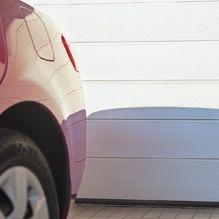 Autó hátulja fehér M–bordatávolság mintás Alutech CLASSIC garázskapu előtt