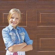 Kislány karba tett kézzel barna kazetta mintás Alutech CLASSIC garázskapu előtt