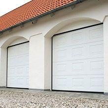 Két fehér kazetta mintás Alutech CLASSIC garázskapu a garázs oldalában