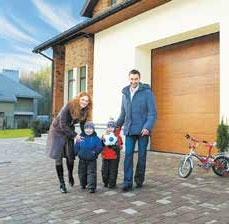 Anyuka, és apuka áll két kisfiúval  garázskapu előtt