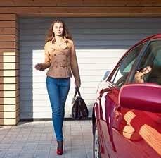 Nő sétál a kocsihoz garázskapu előtt