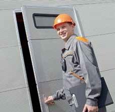 Szervizes férfi munkaruhában kinyitja az irodaajtót