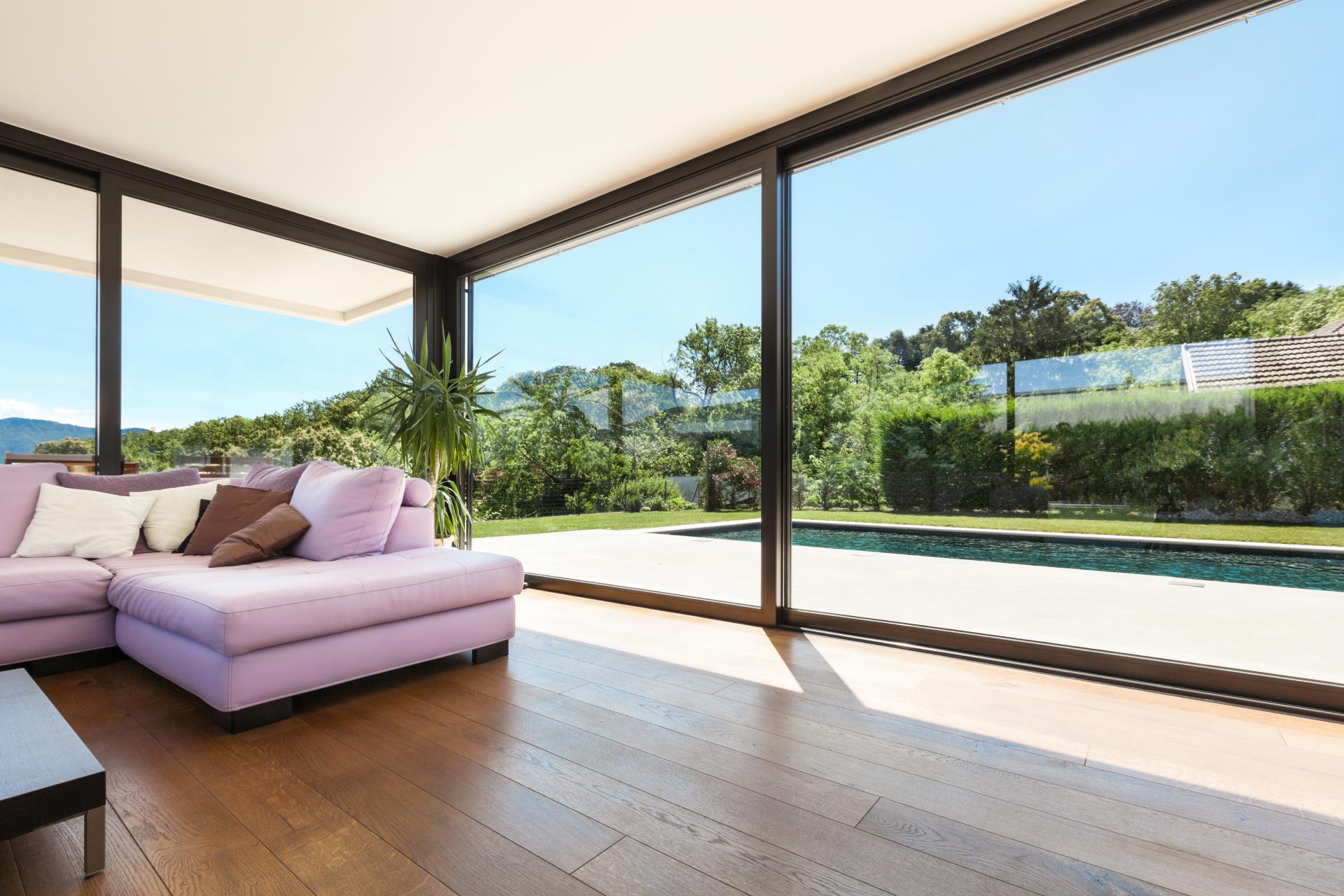 Toló ajtó rendszer luxuslakásban, rózsaszín kanapé mögött, medencés fákkal teli udvarra nézve
