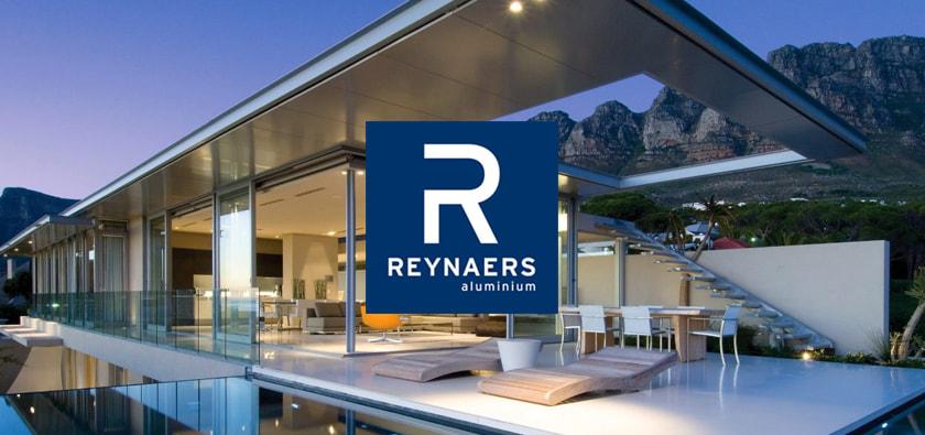 Reynaers márka logó egy modern luxus ház előtt, hegyek a háttérben